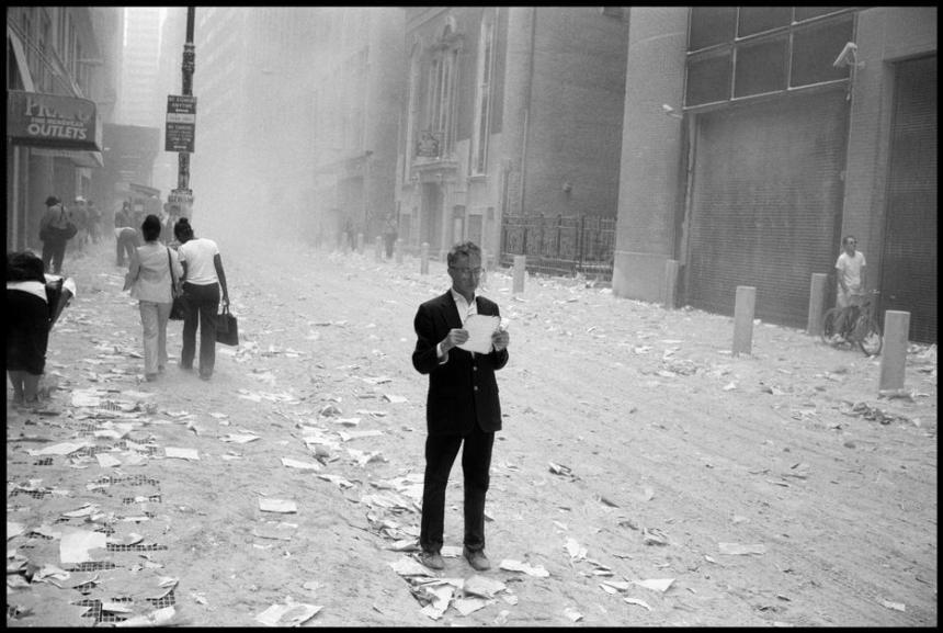 Larry Towell. Un homme hébété ramasse un papier qui a été soufflé hors de tours après l'attaque du World Trade Center, et commence à lire. NYC. 09. 11. 2001
