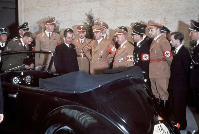 Ferdinand Porsche (costard), A. Hitler, Robert Ley, chef du «Front du travail allemand»,  et les prétendants admirent le cadeau d'anniversaire d'Hitler pour son 50ème anniversaire: une Volkswagen convertible.